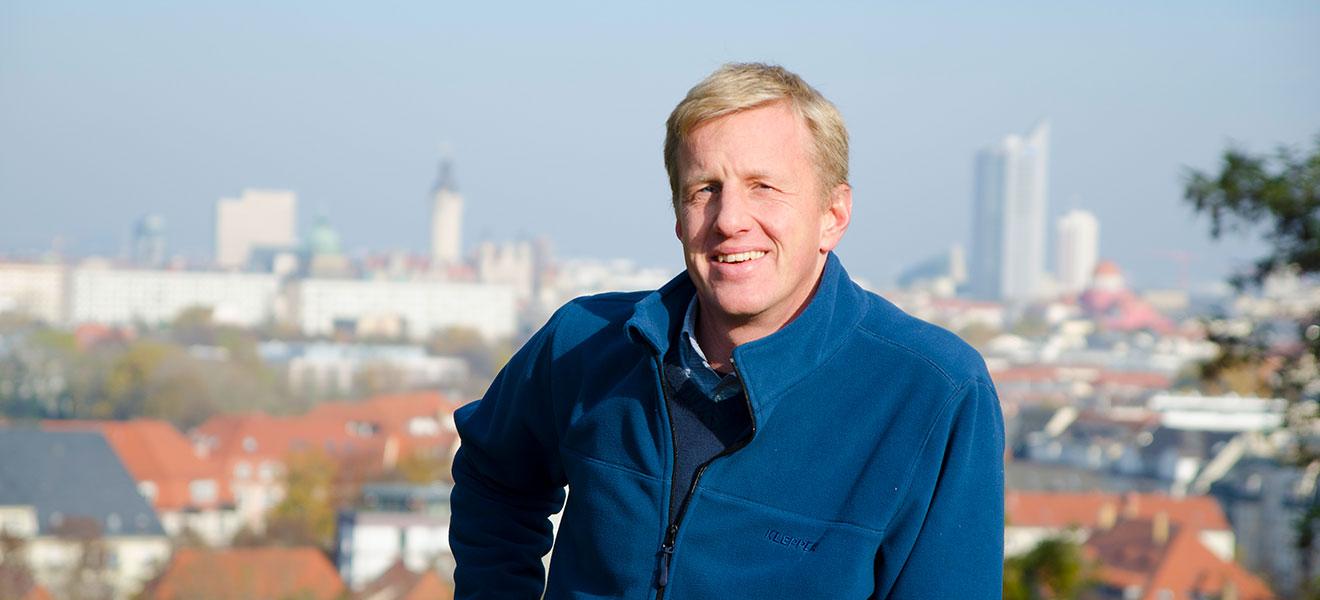 Portrait eines jungen Mannes (Andree Gauer in Persona) mit blauer Fleecejacke und blickt zum Betrachter. Im Hintergrund die Silouette von Leipzig mit Panorama Tower