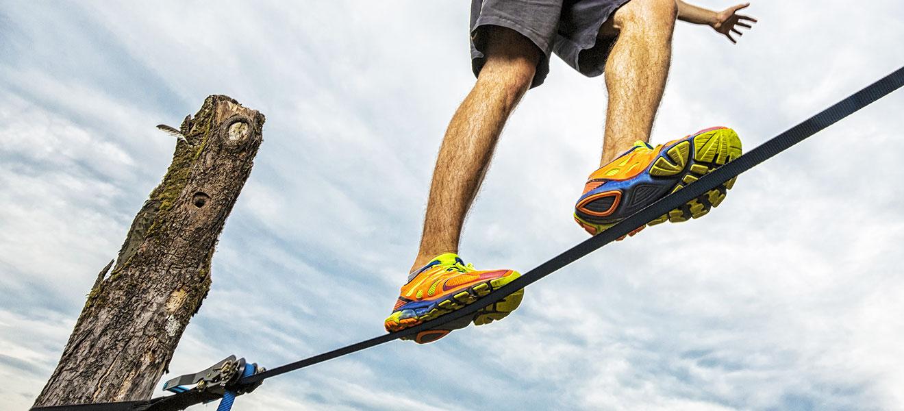 Foto: Beine eines Slackliners mit bunten Turnschuhen auf einer an einem Baumstamm befestigten Slackline. Blick von unten. Hintergrund nur Himmel.