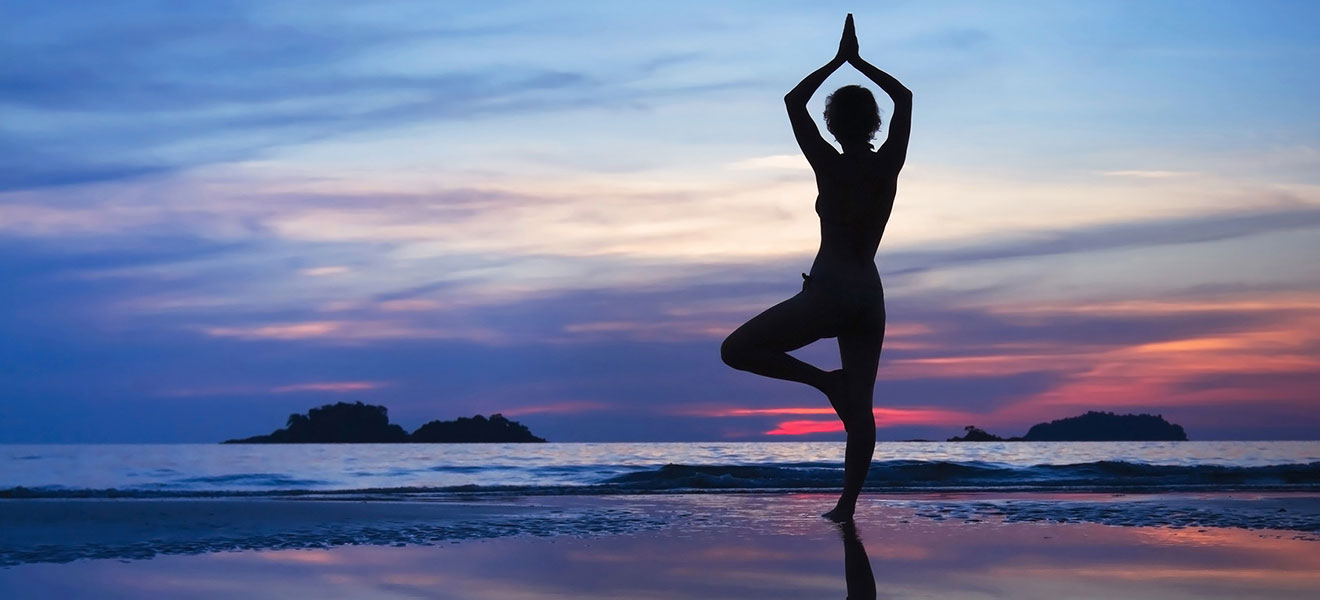 Frau macht Yoga-Baum. Im Hintergrund ein blauer Himmel mit Sonnenuntergang