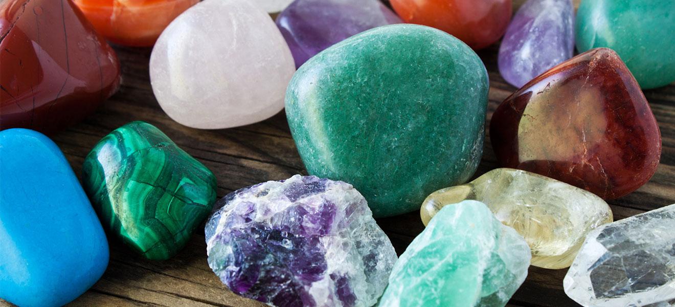 Foto: diverse Edelsteine unterschiedlichster Farbe auf einer Holzunterlage.