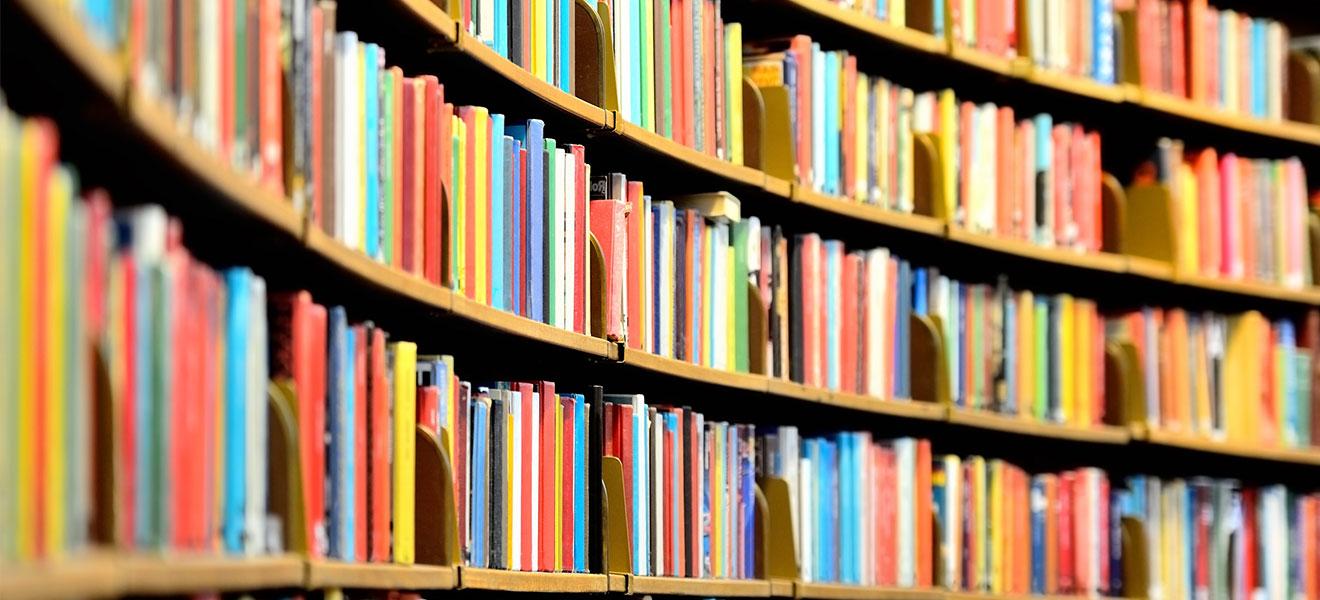 Foto: Bunte Buchrücken in einem nach innen gerundeten Bücherregal einer Bibliothek.