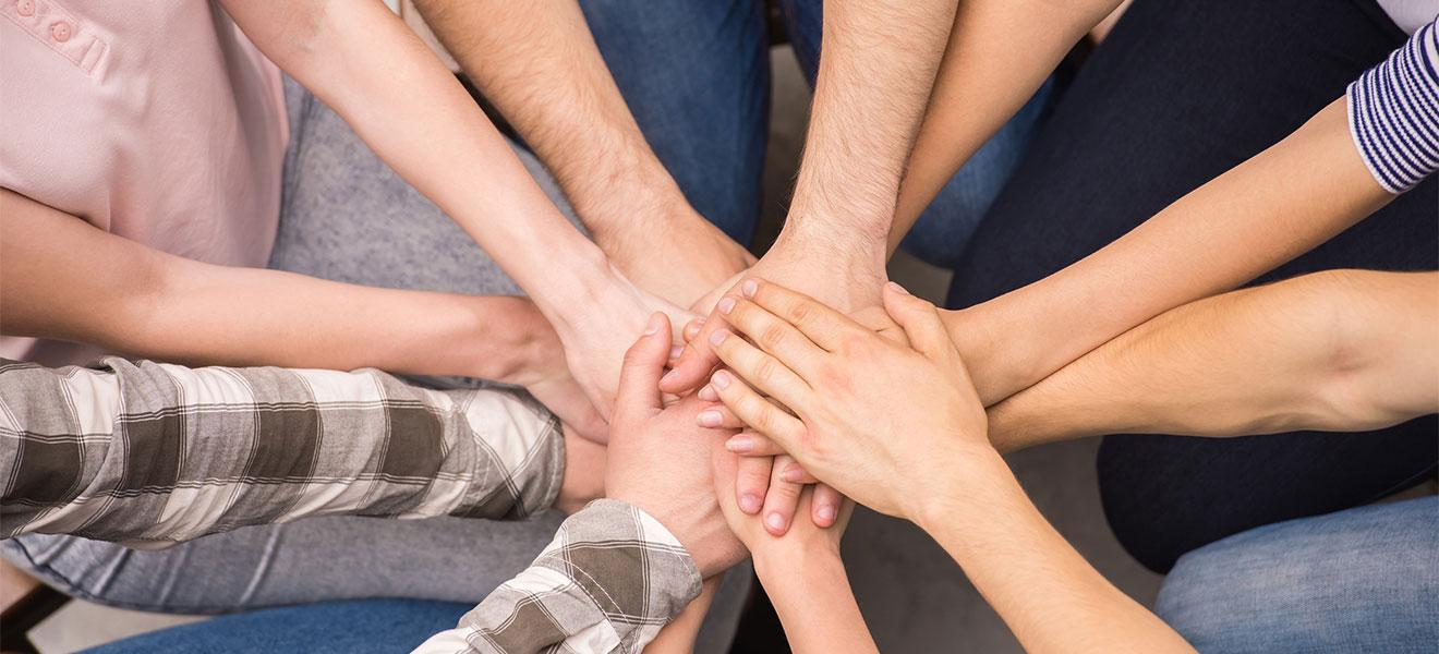 Foto: Die übereinander gelegten Händer von 6 auf einem Fußboden knienden männlichen und weiblichen Personen laufen in der Mitte des Bildes zusammen. Draufsicht von oben.