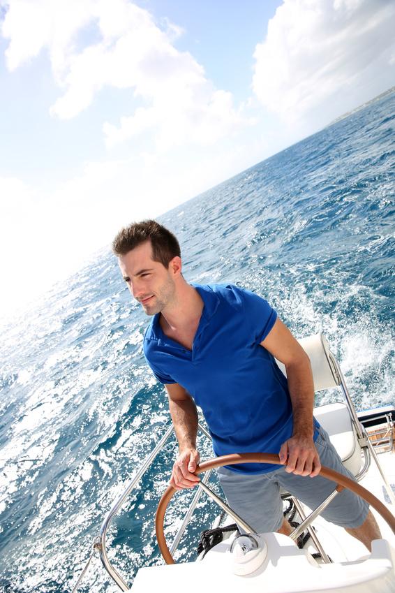Foto: junger Mann in blauem T-Shirt steht am Steuer seines fahrenden Motorboots. Hinter ihm offene See bis zum Horizont. Bild um 45 Grad gedeht.