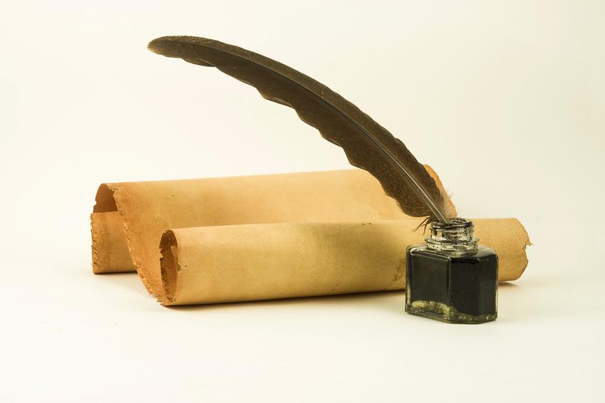 Foto: vergilbte Papierrolle S-förmig gerollt, davor ein Tintenfäßchen aus Glas mit Tinte und einer Feder eingesteckt.