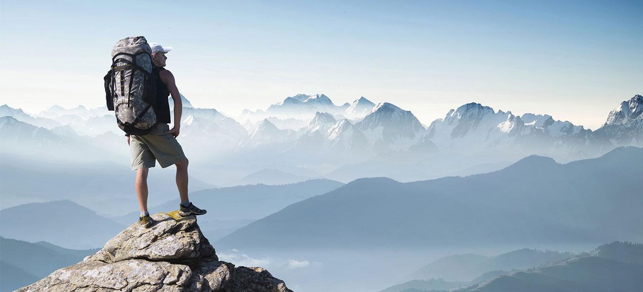 Foto: (Im linken Drittel) Mann in kurzen Hosen und T-Shirt mit großem Trekkingrucksack steht auf ein Bergspitze und schaut auf eine neblige Berglandschaft mit teilweise beschneiten Gifpeln, die sich über das ganze Bild erstreckt.