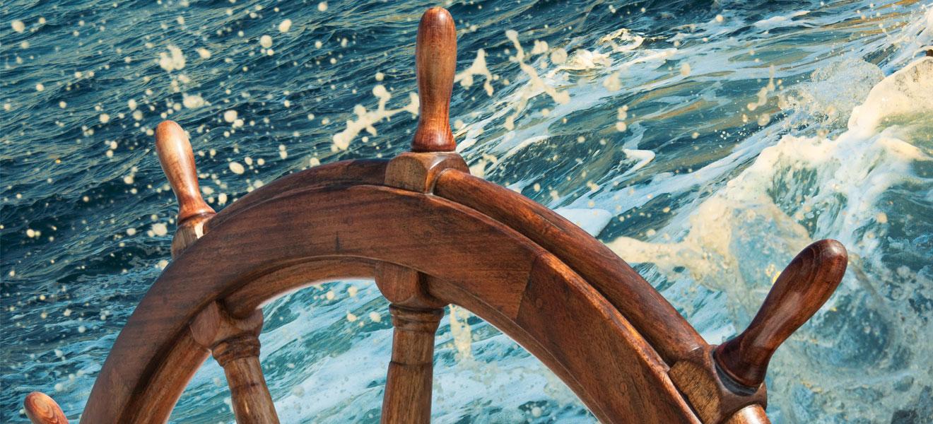 Foto: altes Holzruder- bzw. Steuerad. Aufschäumendens Seewasser im Hintergrund.