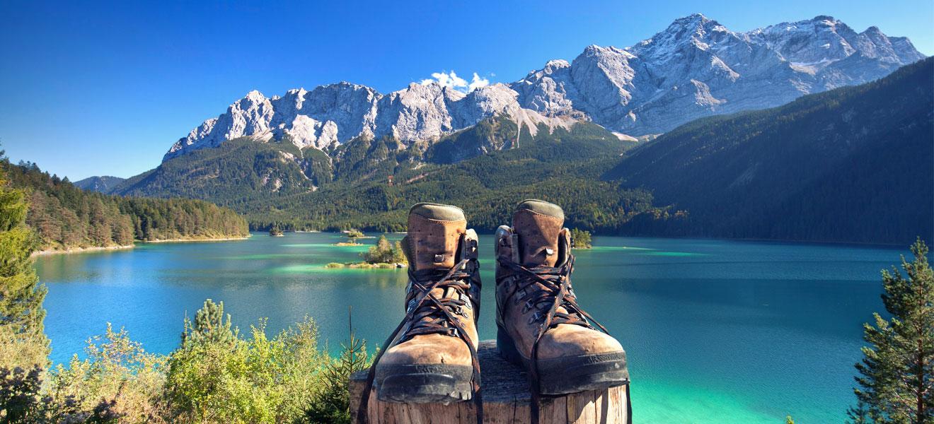 Foto: Leere Wanderstiefel mit überkreuzten herabhängenden Schnürsenkelenden auf einem Holzpfahl im Mittelbereich vorne. Im Hintergrund ein großer blauer See und Berglandschaft.