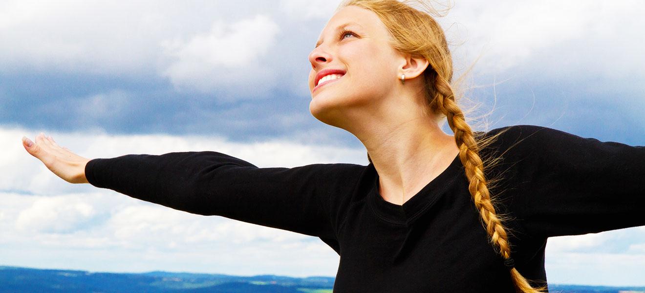 Foto: Junge Frau mit blonden Haaren in schwarzem Langarm-T-Shirt breitet beide Arme in Flugpose und Blick zum Himmel. Hintergrund etwas Horizont sonst nur Wolken.