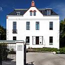 Foto: Zweistöckiges Haus mit weißen Wänden und markantem Dachgiebel unter leicht bedecktem blauen Himmel. Im Vordergrund mittig die Toreinfahrt zwischen weißen Mauern rechts- und linksseitig.