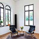Foto: Zimmerecke mit weißen Wänden und 2 großen Fenstern linksseitig und ein großen Fenster rechtsseitig. Im Vordergrund 2 Schwingstühle auf Teppich auf Parkett.