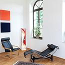 Foto: Zimmerecke mit weißen Wänden und 2 großen Fenstern rechtsseitig und 4 farbigen Quadraten linksseitig. Im Vordergrund auf Parkett ein Schwingstuhl, eine Relaxliege und Sonnenblume in Vase.