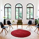 Foto: Großer hoher Raum mit weißen Wänden und 3 hohen Fenstern mit Rundbogen im Hintegrund. Im Vordergrund, mittig im Zimmer 5 Stühle auf Parkett im Halbkreis um roten Teppich.