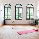 Foto: Großer hoher Raum mit weißen Wänden und 3 hohen Fenstern mit Rundbogen im Hintegrund. Im Vordergrund, mittig im Zimmer 2 Yogamatten auf Parkett.