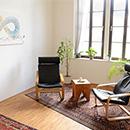 Foto: 2 Schwingstühle um einen kleinen Holzhockertisch auf Perser-Teppichläufer auf Parkettfußboden. Im Hintergrund 2 große Fenster linksseitig und rechtsseitig ein Wandbild.