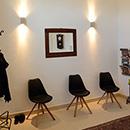 Foto: Foto: 3 Stühle neben Garderobenständer mit Jacke. Darunter ein Paar Schuhe. Mittig ein Bild an der Wand. Rechter Bildrand Durchgang zu den Praxen.