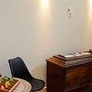 Foto: linker Bildrand Tisch mit Teebeutel-Sortiment. re. daneben Stuhl, re. danaben große Holztruhe. Darüber 2 Wandstrahler. Linker Bildrand oben eine alte Wanduhr.