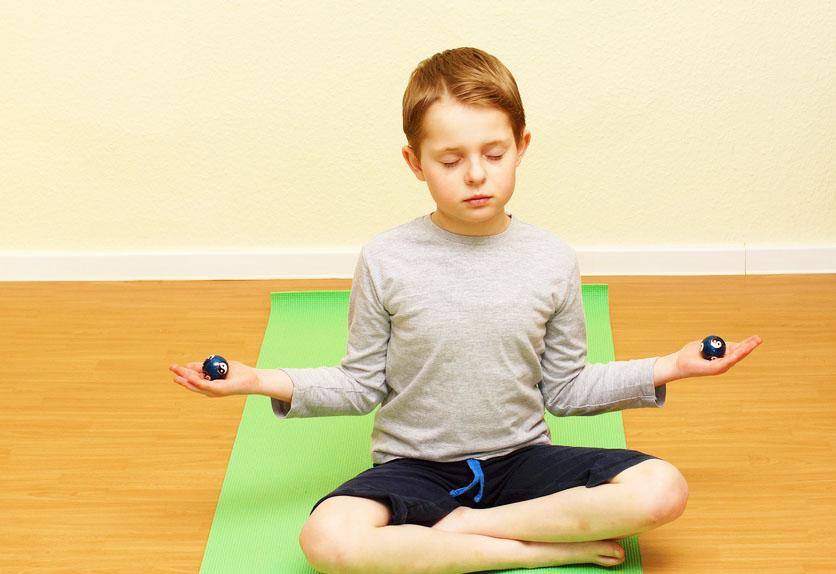 Foto: Kind sitzt mit Vorderseite in Richtung Betrachter auf einer grünen Jogamatte im Schneidersitz mit geschlossenen Augen. Die Ellenbogen jeweils an der Körperseite angewinkelt, die Unterarme waagerecht zum Fußboden, mit je einer Kugel in der Hand.