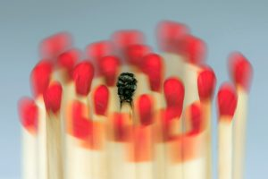 Foto: ca. 20 rote Steichholzkuppen an vertikal ausgerichteten Steichhölzern bewegen sich kreisförmig (bewegungsunschärfe) um einen mittig angeordneten abgebrannten Streichholz.