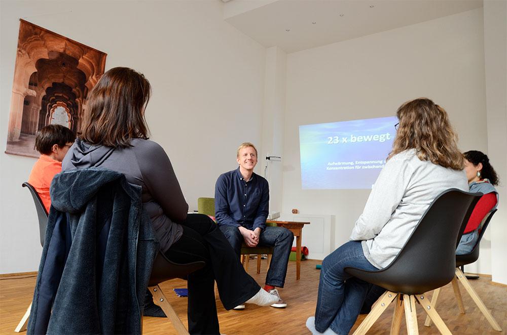 """Foto: 4 Frauen sitzen mit Rücken zum Betrachter im Kreis mit einem jungen Mann in Vorderansicht und kommunizieren. Im Hintergrund rechtseitig an der Wand ein bläuliches Diabild mit Text """"23 x bewegt""""."""