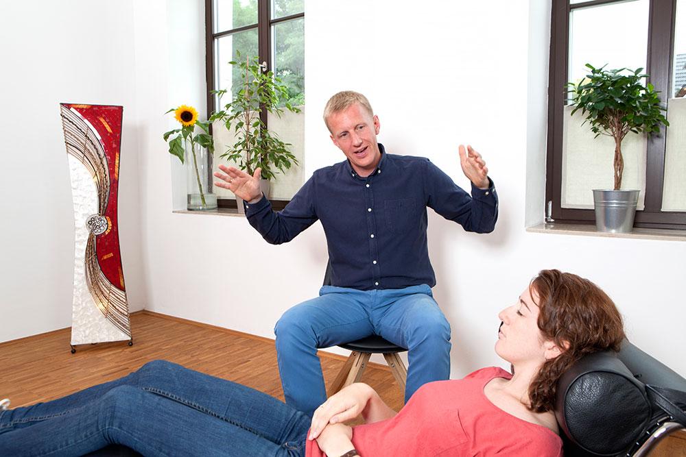 Foto: Junger Mann auf Schemel sitzend mit ausgebreiteten Armen in Bildmitte. Davor quer zu ihm eine junge Frau mit geschlossenen Augen auf eine Relax-Liege. Im Hintergrund weiße Wand mit 2 Fenstern und Pflanzen darin.