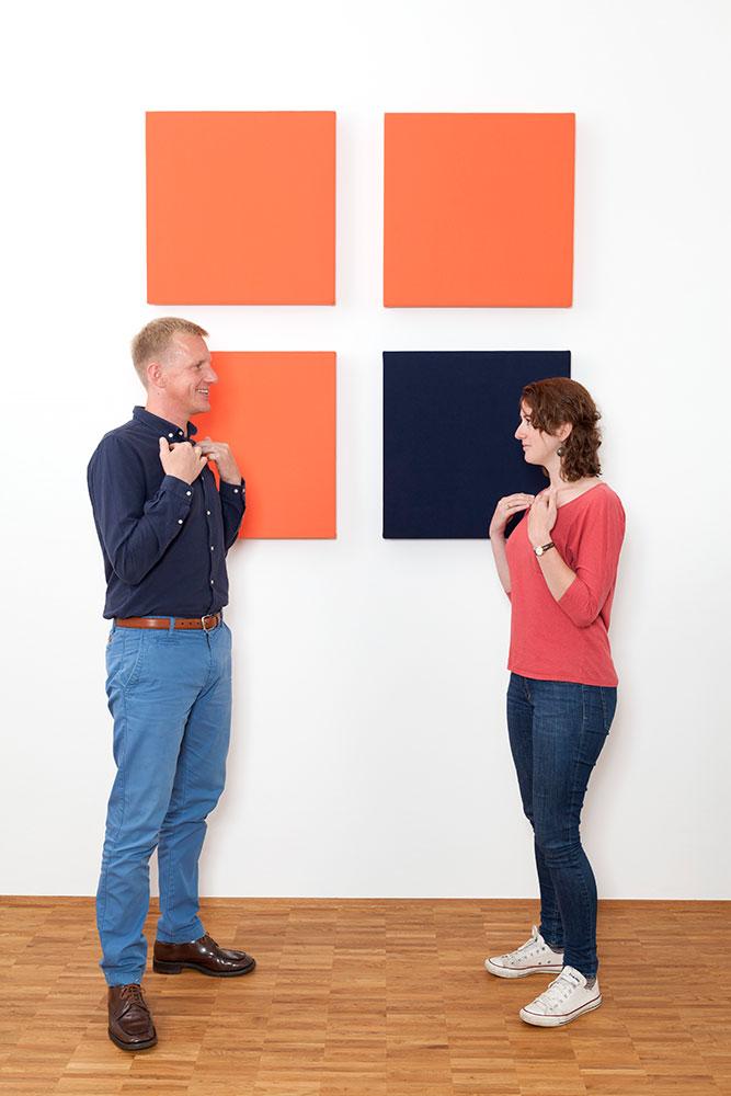 Foto: Junger Mann rechtsseitig, junge Frau linksseitig. Beide stehend auf Parkett mit abgelegten Fingerspitzen oberhalb Brust vor weißer Wand mit 3 orangen und einem blauen Viereck, quadratisch angeordnet.