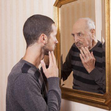 Junger Mann sieht sich älter im Spiegel