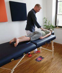 Foto: Kind liegt auf dem Bauch auf Liege, wobei ihm der links danebenstehende behandelnde Psychotherapeut seine rechte Hand auf den Rücken legt.
